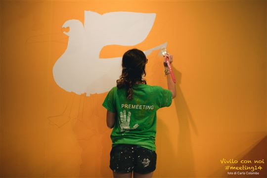 A Rimini Meeting volunteer paints an exhibit wall. Photo by Carlo Colombo via Flickr