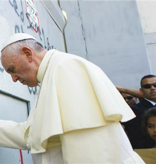 Pope Francis praying in Bethlehem, at the wall that divides Israel and Palestine.