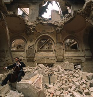 Vedran Smailović playing in the partially destroyed National Library in Sarajevo in 1992. Wikimedia Commons