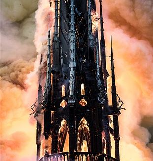 Notre Dame spire on fire. Photo by LEVRIER Guillaume via Wikimedia Commons.